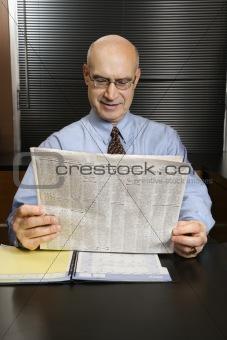 Caucasian businessman reading newspaper.