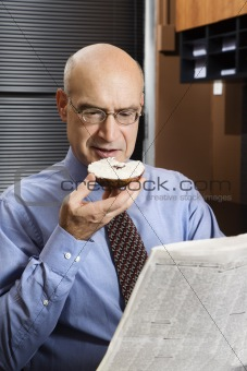 Caucasian businessman eating bagel and reading newspaper.