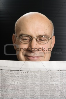 Caucasian man reading newspaper.