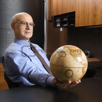 Caucasian businessman holding globe.