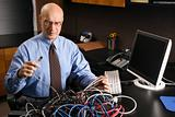 Caucasian businessman with a tangle of computer cables.