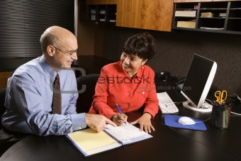 Businessman and businesswoman in office.