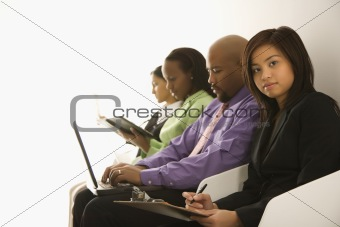 Portrait of businesswoman sitting with others.