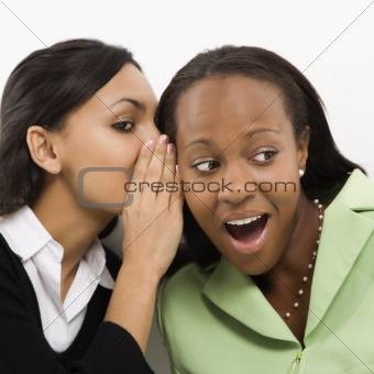 Young woman whispering in ear of mid-adult woman.