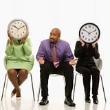 Businesswomen covering faces with clocks and businessman shruggi