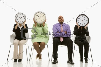 Businesswomen covering faces with clocks with businessman lookin
