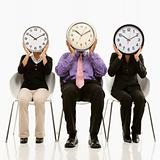 Business people covering faces with clocks.