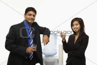 Businessman and businesswoman at water cooler.