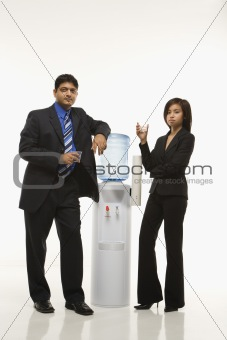 Businessman and businesswoman standing at water cooler.