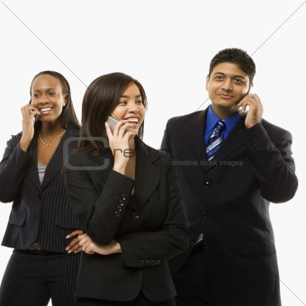 Businesswomen and businessman talking on cell phones.