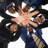 Diverse business people with hands in huddle.