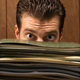 Man peering from behind pile of folders.