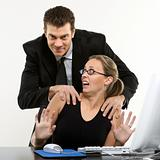 Man harassing woman at computer.