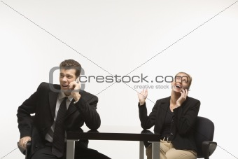 Businessman and woman sitting talking on cell phones.