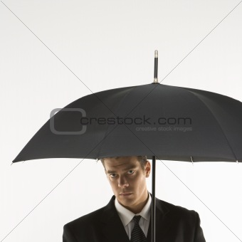 Businessman looking out from under umbrella.