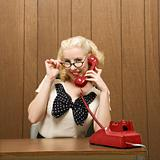 Woman dressed in retro outfit holding a red phone.