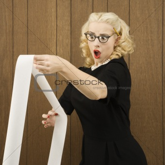 Woman holding a printout with a shocking expression on her face.