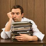 Man with overwhelmed face holding lots of paperwork