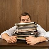 Man peeking over big stack of paperwork.