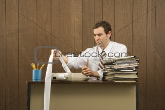 Man holding printout from calculator.