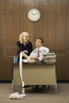 Man holding printout from calculator as woman points.