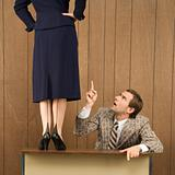 Man pointing up to woman standing on desk.