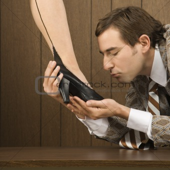 Man holding woman's shoe and preparing to kiss it.