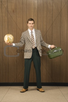 Man in retro suit holding luggage and a globe.