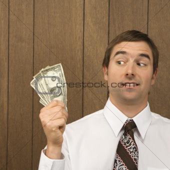 Man holding dollar bills and looking towards them.