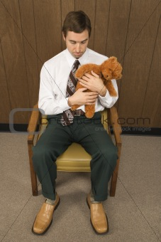Man sitting in chair holding a stuffed animal looking sad.