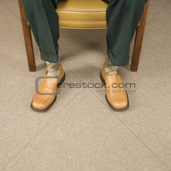 Close up of man sitting in chair wearing retro pants and shoes.