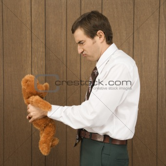 Man holding a stuffed animal and looking upset.