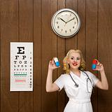 Female nurse in retro uniform holding giant pills.