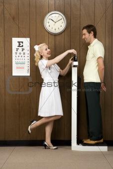 Female nurse weighing man on scale.