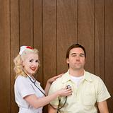 Female nurse checking man's heartbeat.