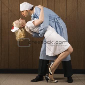 Male surgeon holding female nurse in passionate embrace.