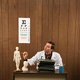 Male doctor at desk with figurine.