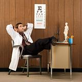 Male doctor with feet on desk.