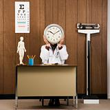 Doctor at desk holding clock over face.
