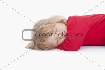 boy with long blond hair lying down sleeping - isolated on white