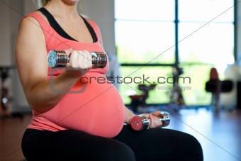 Pregnant woman exercising with weights