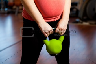 Pregnant woman exercising with a kettlebell