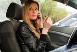 Woman in a car doing makeup.