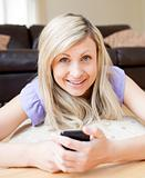 Delighted woman sending a text lying on a bed at home