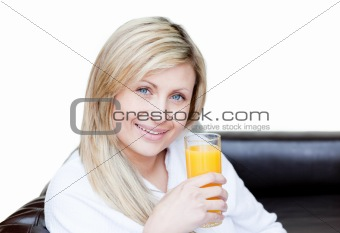 Smiling beautiful woman drinking orange juice in bedroom
