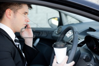 Attractive businessman talking on the phone in a car