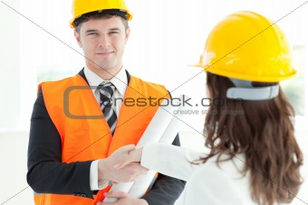 Charismatic architect discussing with his colleague against a white background