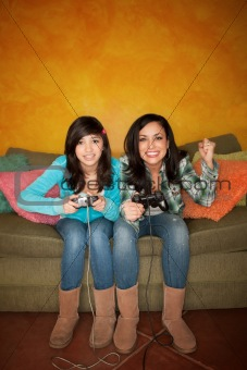 Attractive Hispanic Woman and Girl Playing a Video Game with Handheld Controllers