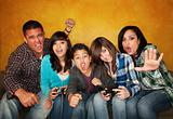 Attractive Hispanic Family on Couch Playing a Video Game