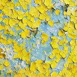 Yellow wall covered with scraps of paint